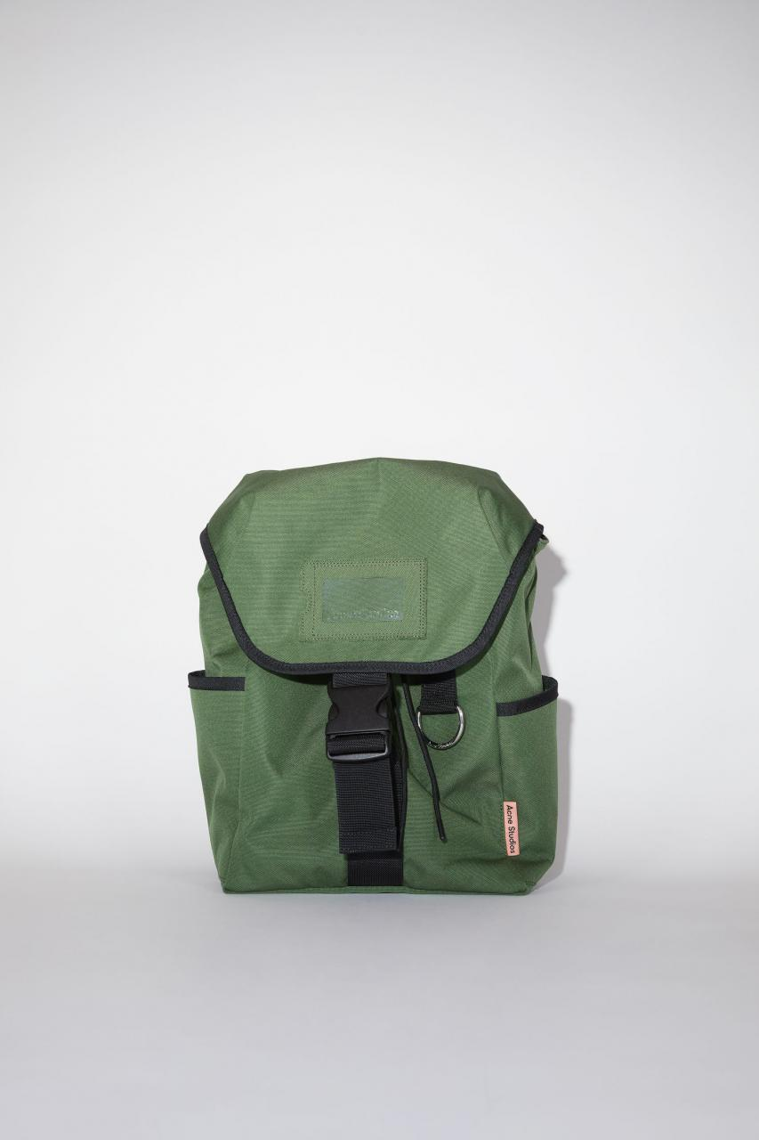 Acne Studios dark green durable backpack has a clear vinyl ID pocket, two generous side pockets, adjustable straps, and an Acne Studios logo tab. 001